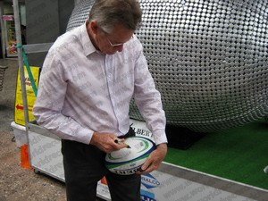 Sir John Walker signing rugby ball at the bottle cap sculpture launch 3rd December 2010